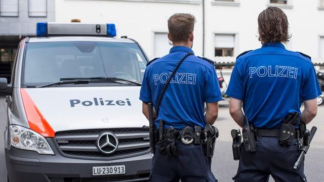 Zwei Polizisten in blauer Uniform vor einem Polizeiauto.