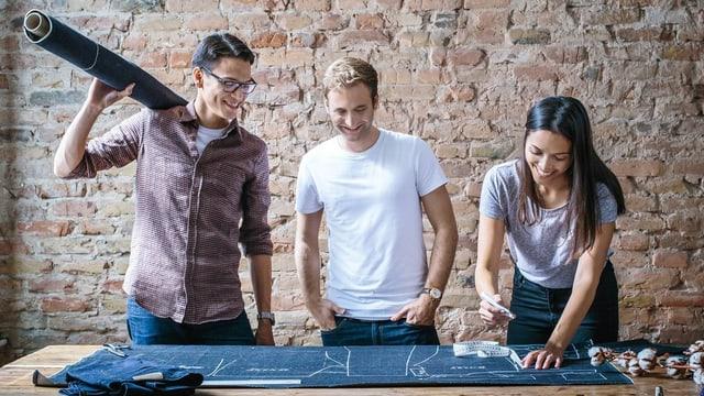 Drei Menschen schneidern eine Jeans.