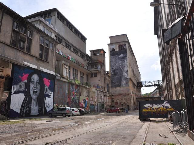 Indistrieareal mot hohen Hallen. Graffitis an den Wänden.