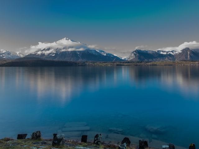 Glatte Seeoberfläche, am anderen Ufer ein Berg mit Schnee auf dem Gipfel, der Niesen.