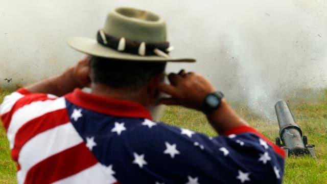 Kanone, dahinter Mann mit T-Shirt, das die US-Flagge zeigt.