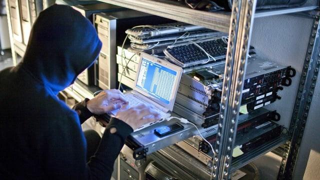 Symbolbild, ein Hacker sitzt an einem Computer und programmiert Codes.