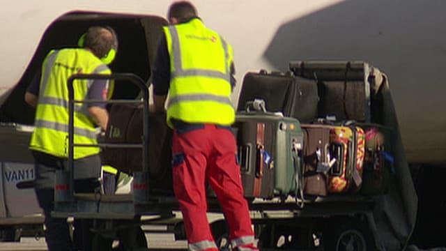 Zwei Gepäckarbeiter mit gelber Warnweste beladen von Hand ein Flugzeug mit Gepäck, das auf einem Wagen liegt