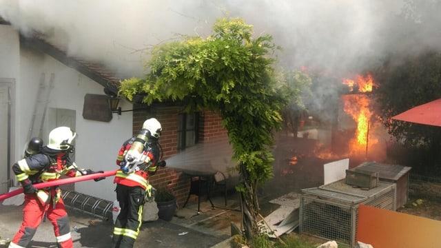 Feuerwehrleute mit Schlauch bekämpfen Feuer