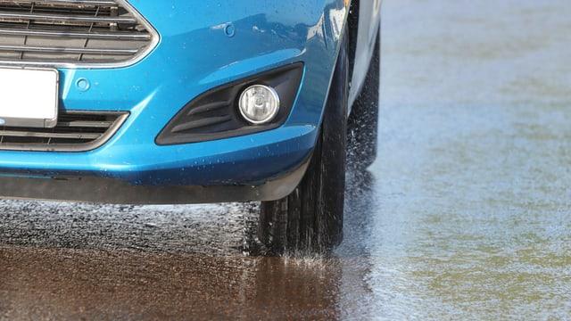Nahaufnahme Autoreifen auf nasser Fahrbahn.