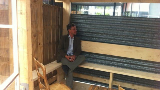 Der Archtekt Christophe Scheidegger sitzt in einer seiner Hütten aus Holz und Wellblech in einer Ecke.