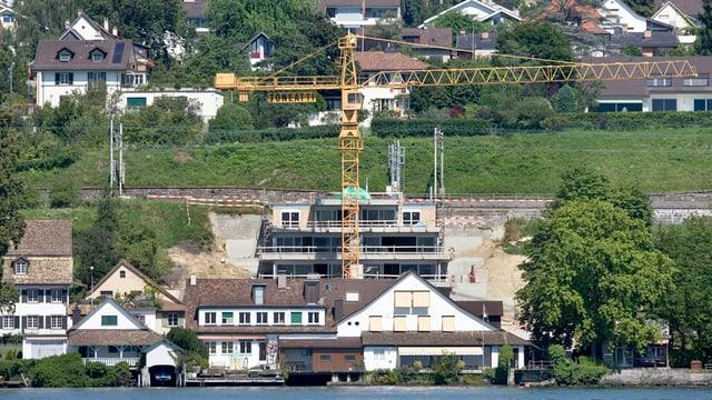 Ein gelber Kran steht zwischen der Bahnlinie und Häuser am Ufer des Zürichsees.