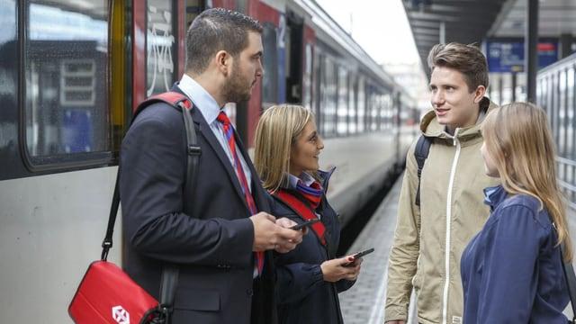 Zwei SBB-Angestellte beraten zwei Reisende im Bahnhof Basel.