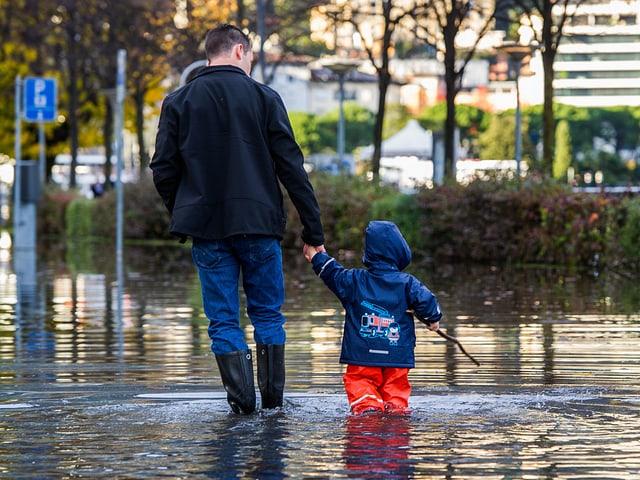 Mann mit Kind im Hochwasser