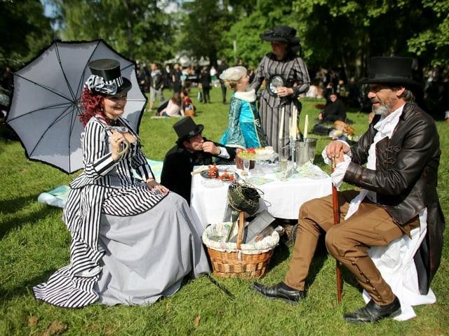 Menschen in viktorianischen Kleidern machen im Park ein Picknick.