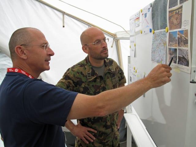 Zwei Männer stehen vor einer mobilen Wandtafel und sprechen über Bilder eines Erdbebens.