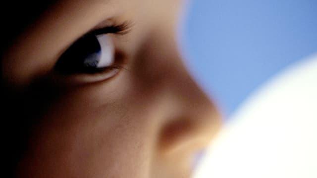 Nahaufnahme: Kleines Kind blickt ängstlich nach hinten.