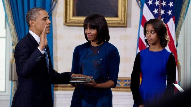 Barack Obama, Hand nach oben haltend, Michele Obama (m) Bibel haltend, Tochter Malia (r)