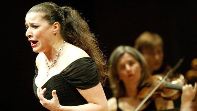 Sängerin in schwarzem Kleid mit langen braunen Haaren singt auf der Bühne