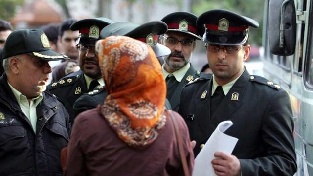 Polizeisten stehen um eine Frau herum.