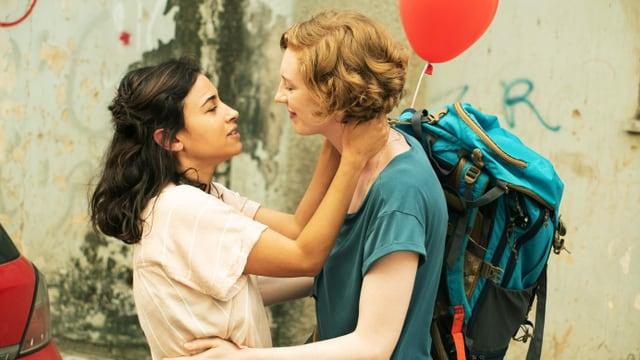 Filmausschnitt: Zwei Frauen auf der Strasse halten sich in den Armen und schauen sich an. Eine grosse rothaarige und eine kleine braunhaarige.