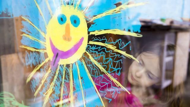 Ein Mädchen malt eine Sonne, welche die Zunge herausstreckt, auf ein Fensterglas.