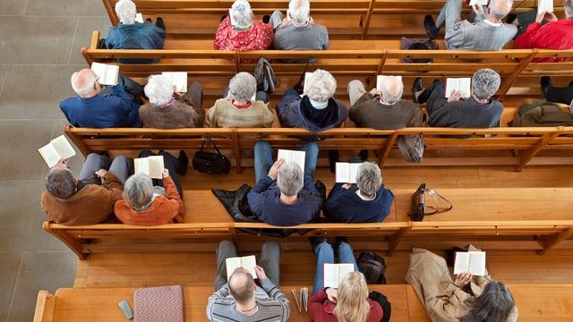 Kirchenbank von oben. Vor allem ältere Menschen sitzen in einer Reihe.
