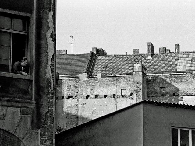 Auf einer schwarz-weissen Fotografie sieht man einige triste Häuserfronten, aus einem Fenster schaut ein Mann.