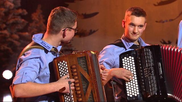 Zwei junge Akkordeonisten in blauen Hemden beim Musizieren.