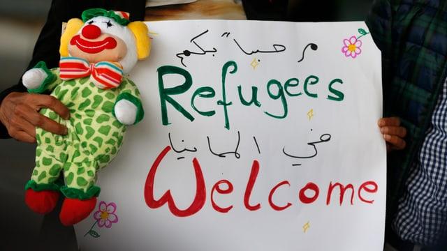 Eine Frau mit einem Transparent auf dem «Refugees welcome» steht.