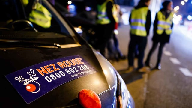 Ein Auto mit der Aufschrift Nez Rouge und Verkehrspolizisten im Hintergrund.