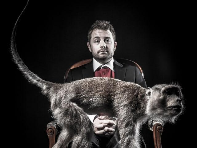 Gabriel Vetter sitzt in einem Sessel (Anzug, Hemd). Auf seinem Schoss: Ein Affe.