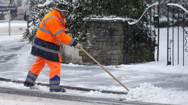 Ein Mitarbeiter des Strasseninspektorats räumt einen verschneiten Gehweg mit der Schaufel.