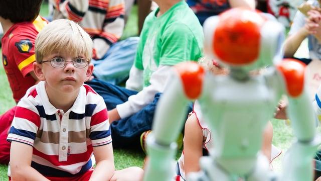 Ein Kind sitzt mit grossen Augen vor einem Roboter.
