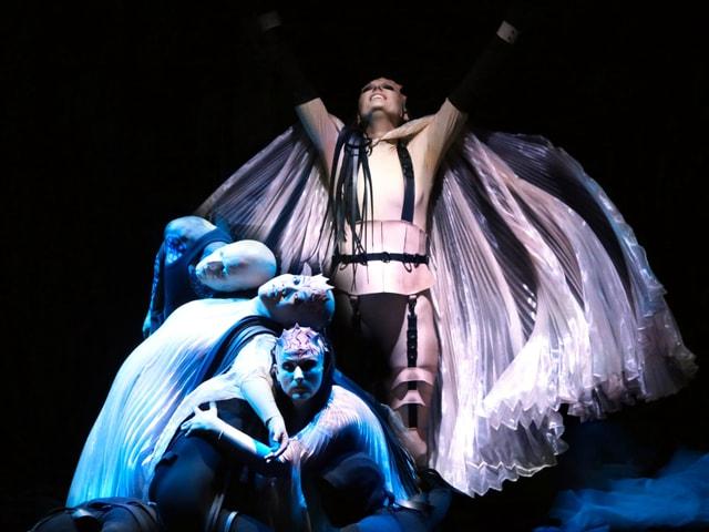 Personen in weissen Gewändern in einer Opernszene.