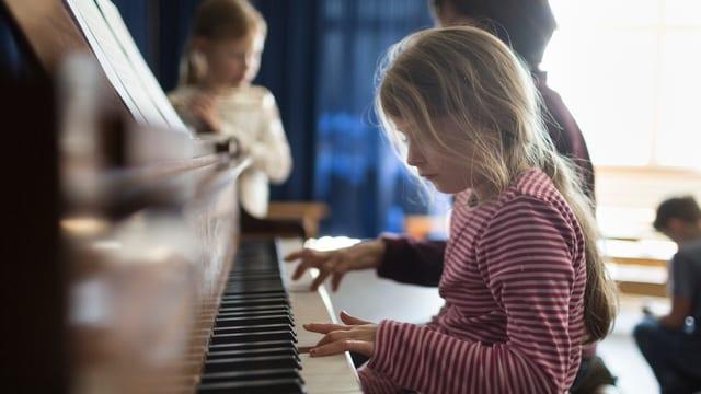 Mädchen spielt auf einem Klavier