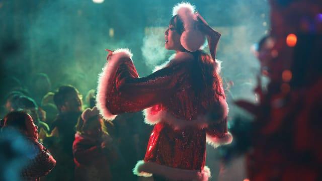 Eine Chinesin im Weihnachtskostüm auf der Bühne.