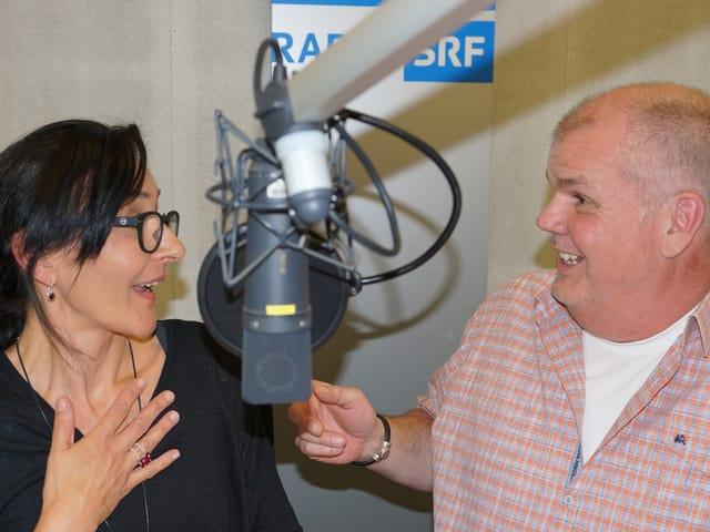 Eine Frau und ein Mann lachend vor einem Mikrofon.