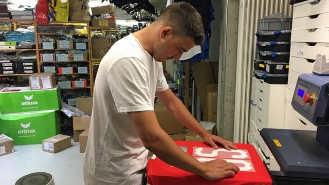 Ein Verkäufer macht ein Leibchen für den Aufdruck der Trikotnummer und des Namens bereit.