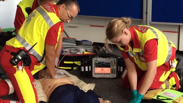 Drei Personen in Leuchtwesten knien am Boden und machen an einer Puppe eine Herzmassage.