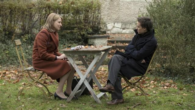 Filmstill: Eine Frau und ein Mann sitzen an einem Gartentisch.