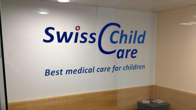 Logo des Swiss Child Care Zentrums in Rothrist, auf der Glaswand des Wartezimmers