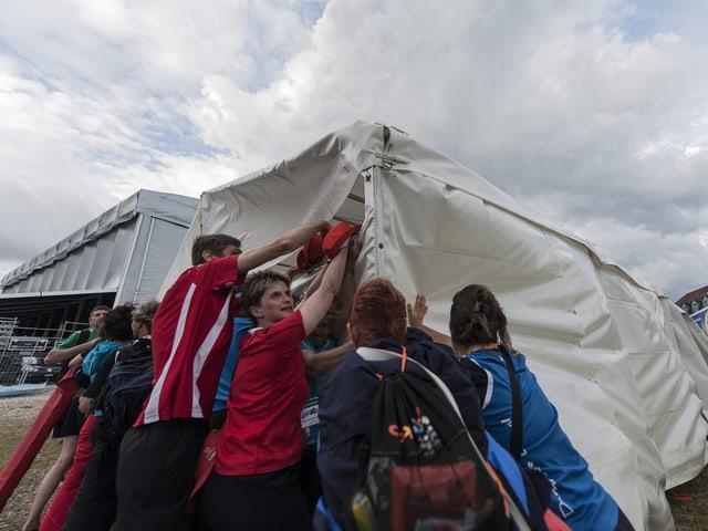 Besucher des Turnfestes hielten Zeltstangen fest, um sie vor dem Davonwinden zu bewahren.