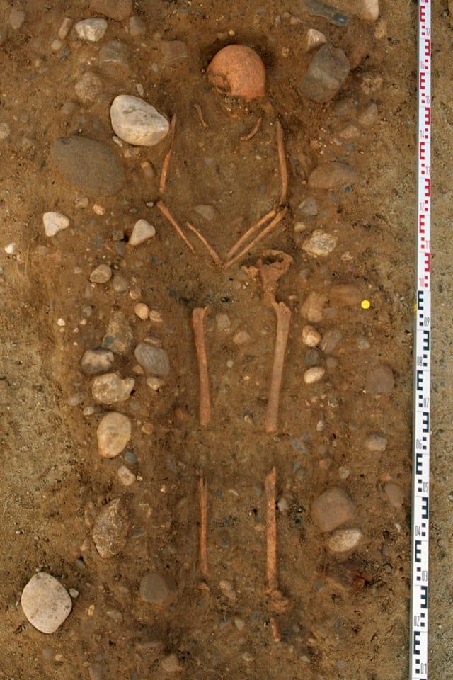 Ein Grab mit einzelnen Knochen.