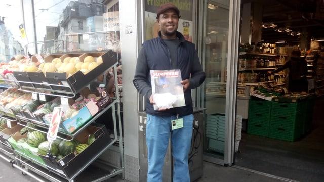 ein dunkelhäutiger Mann verkauft das Strassenmagazin Surprise