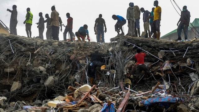 Helfer stehen auf den Trümmern einer Kirche