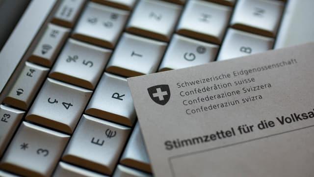 Auf einer Computertastatur liegt ein Stimmzettel für die Volksabstimmung