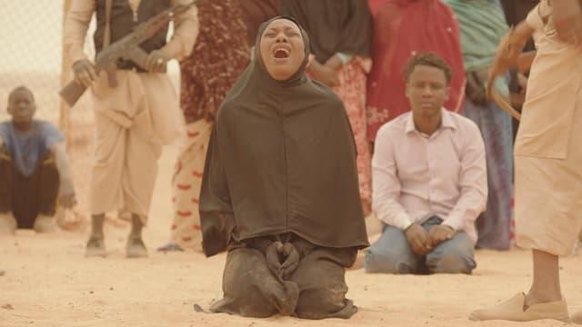 Eine Frau in schwaruem Gewand und Kopftuch kniet schreiend im Sand.