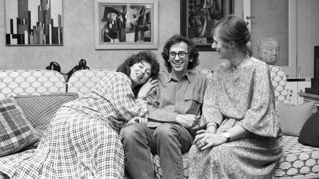 Zwei Frauen und ein Mann lachend auf einem Sofa.