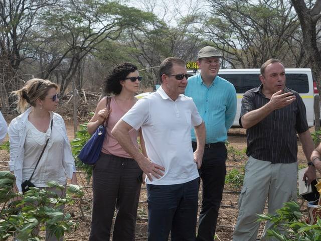 Vier Personen stehen herum, ein Mann in weissem T-Shirt hat die Hände in die Hüften gestützt.