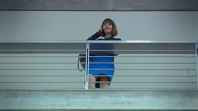 Frau telefonierend, von unten gefilmt.