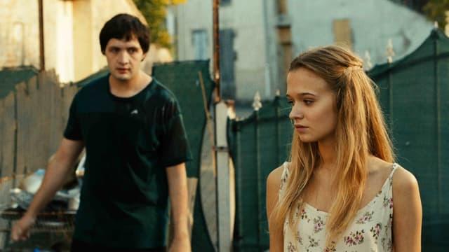 Ein Junge schaut ein Mädchen an auf einem Hinterhof mit Bretterzäunen