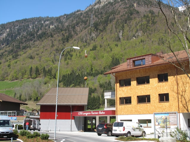 Die neue rote Talstation der Lungen-Turren-Bahn mit Wohnhaus und Autos