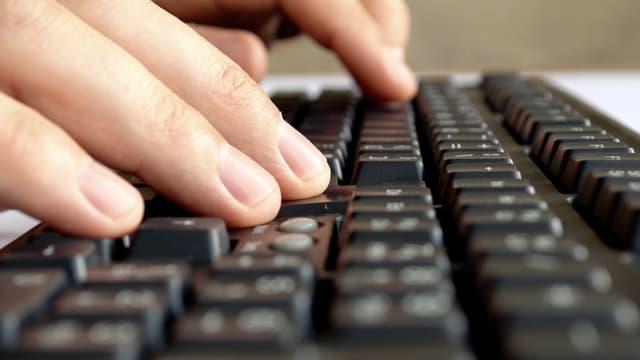 Tippende Finger auf einer schwarzen Computertastatur.