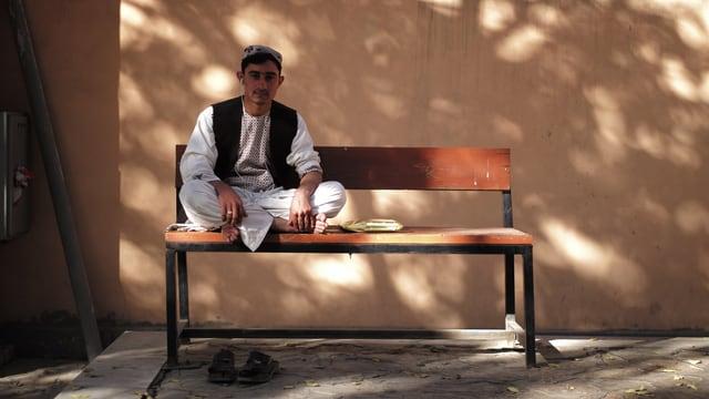 Junger Mann sitzt auf Bank und hört Musik mit Kopfhörern.